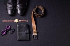 Gli accessori del ` s degli uomini su fondo nero legano lo sho del cinturino di orologio del portafoglio Fotografia Stock