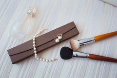 Gli accessori della donna si chiudono su: componga la spazzola, gli orecchini, il braccialetto ed il profumo Fotografia Stock