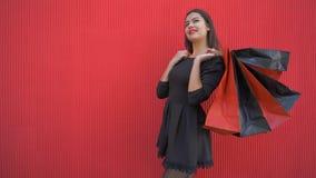 Gli acquisti felici, donna riflettente con molti sacchetti della spesa pensa che cosa comprare allo sconto il venerdì nero stock footage