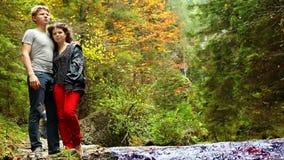 Gli adolescenti attraenti accoppiano sorridere vicino alla torrente montano con il fondo variopinto di autunno archivi video