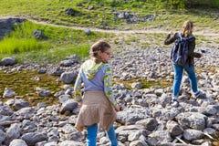 Gli adolescenti con gli zainhi attraversano prudentemente The Creek lungo le rocce, facenti un'escursione nelle vacanze estive de fotografie stock