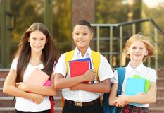 Gli adolescenti con gli zainhi ed i taccuini sulla scuola estasiano il fondo immagini stock libere da diritti