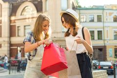 Gli adolescenti delle ragazze in via della città esaminano gli acquisti in sacchetti della spesa Fotografie Stock