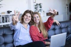 Gli adolescenti felici che si siedono su un sofà con un computer portatile che fa la vittoria firmano immagini stock