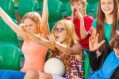 Gli adolescenti incoraggiano per il gruppo durante il gioco allo stadio Fotografie Stock