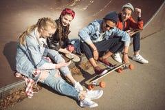 Gli adolescenti raggruppano la seduta di seduta insieme e per mezzo dei dispositivi digitali fotografia stock