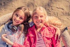 Gli adolescenti sorridenti graziosi si siedono la menzogne insieme immagini stock libere da diritti