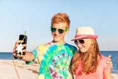 Gli adolescenti stanno facendo l'autoritratto e la musica d'ascolto Immagine Stock