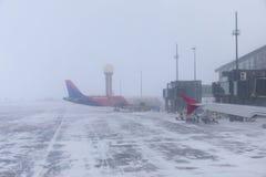 Gli aerei sulla pista durante la bufera di neve immagine stock