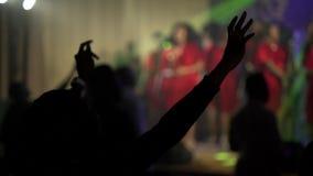 Gli africani neri pregano nella sala da concerto Mani di aumento e di ballo su Fucilazione tramite le vostre mani nella lampadina video d archivio