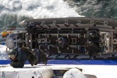 Gli agenti dello SCHIAFFO arrampicano in su il lato di una nave Fotografia Stock