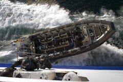 Gli agenti dello SCHIAFFO si arrampicano mentre la barca di sostegno taglia via Fotografia Stock