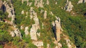 Gli aghi di pietra della roccia attaccano dalla foresta sul fianco di una montagna Vista dell'occhio del ` s dell'uccello archivi video