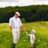 Gli agricoltori del figlio e del padre che camminano lungo le patate rema fra i campi verdi Fotografia Stock Libera da Diritti