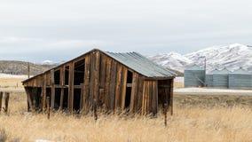 Gli agricoltori di legno anziani hanno sparso su una strada rurale nell'inverno Fotografie Stock