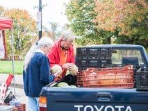 Gli agricoltori esaminano i prodotti del melone nel loro letto di camion al segno degli agricoltori Immagini Stock Libere da Diritti