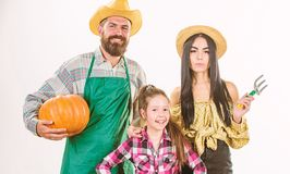 Gli agricoltori rustici di stile della famiglia fieri dei genitori e della figlia del raccolto di caduta celebrano la zucca di fe fotografie stock