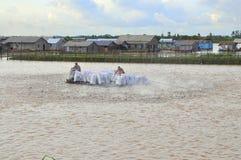 Gli agricoltori stanno alimentando il pesce gatto di pangsius nel loro stagno nel delta del Mekong del Vietnam Immagini Stock