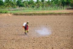 Gli agricoltori stanno spruzzando il diserbante nel campo prima della piantatura Immagini Stock Libere da Diritti