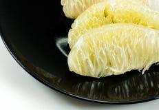 Gli agrumi verdi del pomelo sul piatto nero Fotografia Stock
