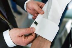 Gli aiuti dell'amico del ` s dello sposo fissano i gemelli sulla manica del ` s dello sposo fotografia stock