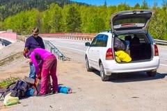 Gli aiuti dell'autista scaricano lo zaino della donna dell'autostoppista nell'automobile Fotografia Stock