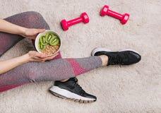 Gli alci di sport della ragazza placcano le teste di legno di allenamento di forma fisica del kiwi di muesli Immagini Stock