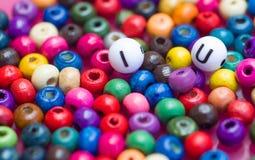 Gli alfabeti I ed U circondati da molte perle variopinte Immagini Stock