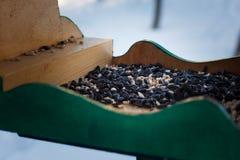 Gli alimentatori per gli uccelli nella neve dell'inverno fanno il giardinaggio con i semi di girasole Immagine Stock Libera da Diritti