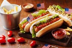Gli alimenti a rapida preparazione dal hot dog con la salsiccia e le fritture hanno decorato la bandiera di U.S.A. il 4 luglio Re immagini stock