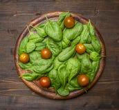 Gli alimenti sani, cucinare e gli ingredienti vegetariani di concetto per l'insalata, spinaci freschi va, pomodori ciliegia, pres Fotografia Stock