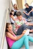 Gli allievi che comunicano la distensione sul banco fa un passo anni dell'adolescenza Fotografia Stock