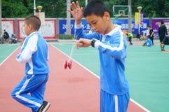 Gli allievi cinesi stanno giocando il yo-yo Immagini Stock
