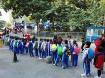Gli allievi cinesi svolgono le attività fuori della scuola e sono sul modo Fotografie Stock