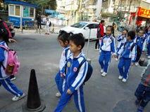 Gli allievi cinesi svolgono le attività fuori della scuola e sono sul modo Immagini Stock