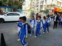 Gli allievi cinesi svolgono le attività fuori della scuola e sono sul modo Fotografia Stock Libera da Diritti
