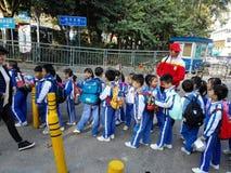 Gli allievi cinesi svolgono le attività fuori della scuola e sono sul modo Immagini Stock Libere da Diritti