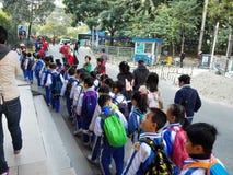 Gli allievi cinesi svolgono le attività fuori della scuola e sono sul modo Immagine Stock