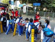 Gli allievi cinesi svolgono le attività fuori della scuola e sono sul modo Fotografia Stock