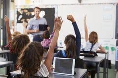 Gli allievi con le mani si sono alzati nella classe della scuola elementare Fotografia Stock
