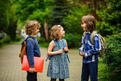Gli allievi della scuola elementare circa qualcosa allegramente parlano sul cortile della scuola Fotografia Stock
