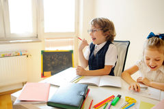 Gli allievi della scuola primaria stanno sedendo allo stesso scrittorio Fotografia Stock