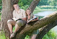 Gli allievi hanno letto i libri sulla banca del lago Fotografia Stock Libera da Diritti