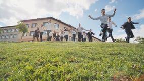 Gli allievi senior felici si allontanano dalla collina sui precedenti della loro scuola fotografie stock