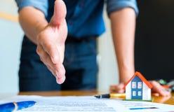 Gli allungamenti domestici del rappresentante a stringe le mani, la casa del modello e della penna sulla h Immagine Stock