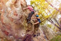 Gli alpinisti scala una roccia con i cablaggi in terreno boscoso Immagini Stock Libere da Diritti