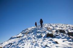 Gli alpinisti scalano il pendio nevoso Fotografie Stock