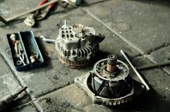 Gli alternatori hanno messo a parte per la riparazione con il contenitore di strumenti. Immagine Stock Libera da Diritti