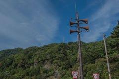 Gli altoparlanti hanno trasmesso per radio la torre con un cielo blu e un fondo della montagna Fotografia Stock