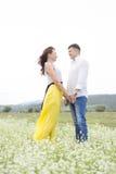 Gli amanti equipaggiano e la passeggiata della donna sul giacimento di fiore Fotografie Stock